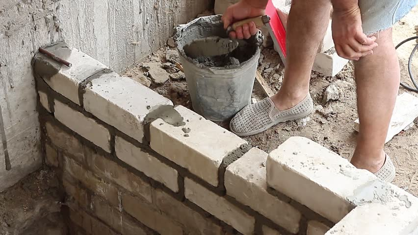 Builder puts a spatula the cement-sand mixture for further bricklaying