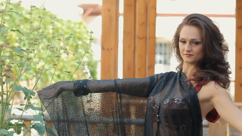 Talented girl dancing oriental dance next to the gazebo in the garden - HD stock video clip