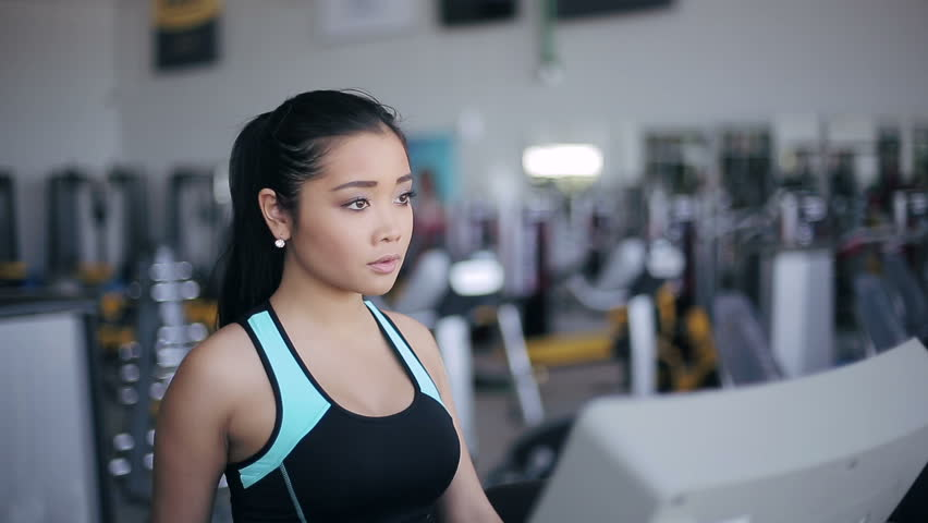 Attractive asian girl running on the treadmill in the gym. Right 3/4 face portrait - HD stock footage clip