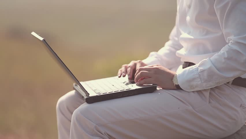Attractive caucasian race professional man working on a laptop computer alone in nature with his thoughts extreme close up shoot.