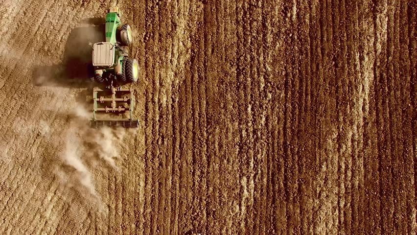 Aerial: Lonely tractor plow the wheat field Plow the field.