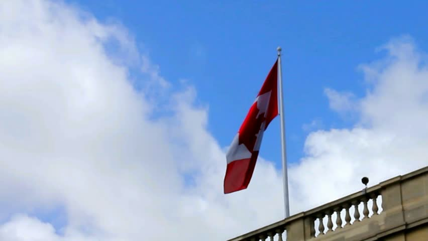 Flag of Canada flying on blue sky background. - HD stock footage clip