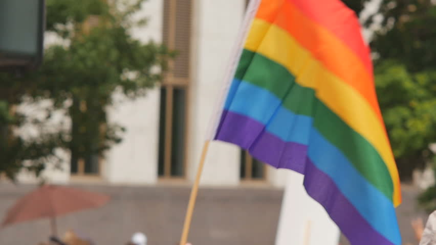 A rainbow flag waves as people walk by in the background with other rainbow flags and protest signs.
