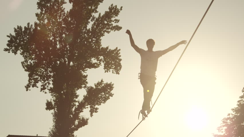 SLOW MOTION: Young unrecognizable man walking on high slackline at beautiful summer sunset