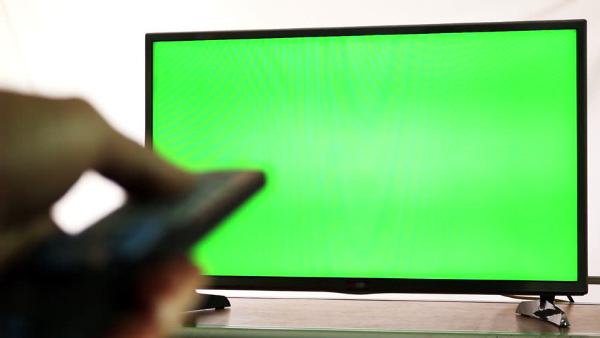 Male hand with TV remote switching channels on green screen TV point of view