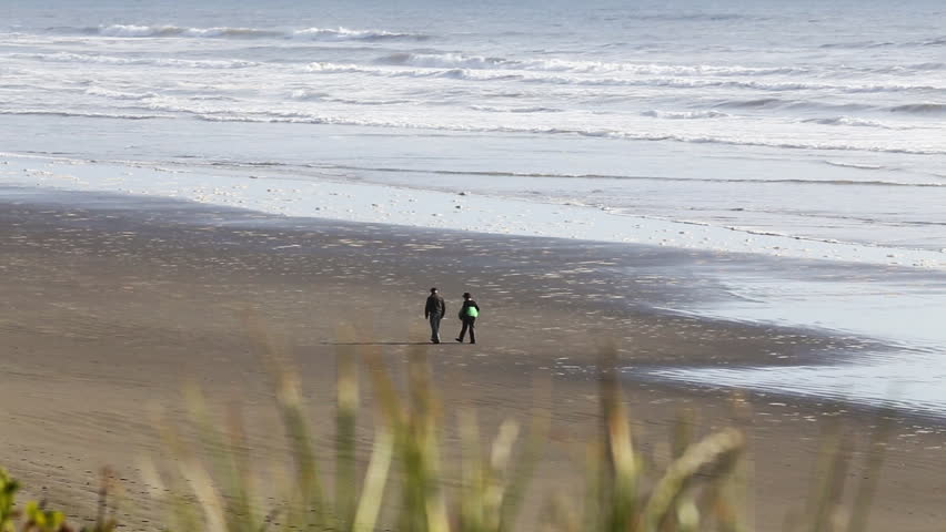 Couple walking out of frame on the beach