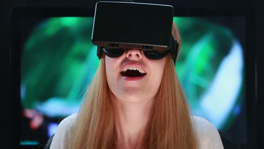 Virtual reality game. Girl with pleasure uses head-mounted display.