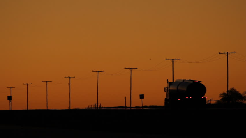 Trucks at dusk travelling on TransCanada Highway 1. Saskatchewan, Canada.