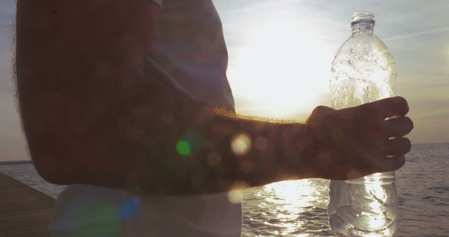 Steadicam shot of a young man refreshing with a water from the bottle outdoor. He having drink on the background of sea and evening sky with bright sunset - 4K stock footage clip