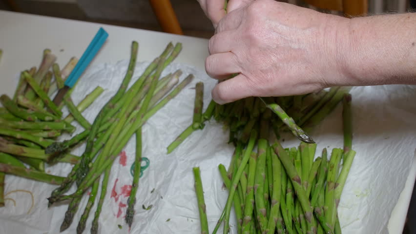 old woman cutting and peeling asparagus