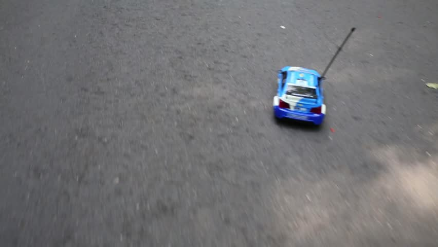 Radio controlled toy car moves on asphalt road at summer
