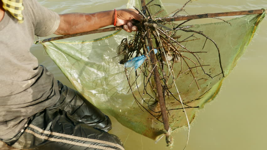 Close-up on prawn fisherman baiting net, dropping and pushing it deeper into river with paddle for a catch, southeast asia, cambodia