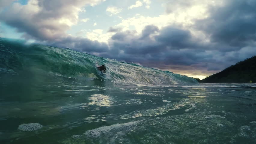 Surfer on Blue Ocean Wave Getting Barreled and Wiping Out. Shore Break.