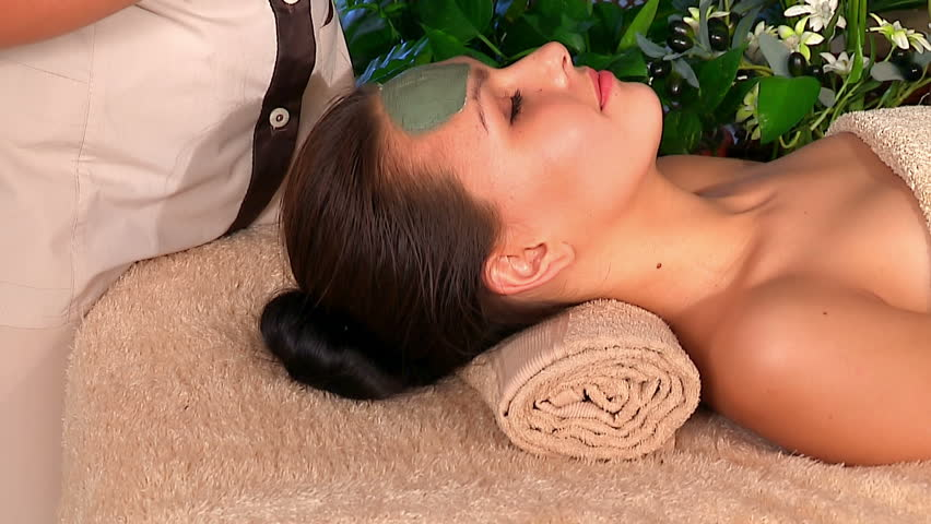 Beautician is applying facial clay mask woman  in beauty spa. - HD stock footage clip