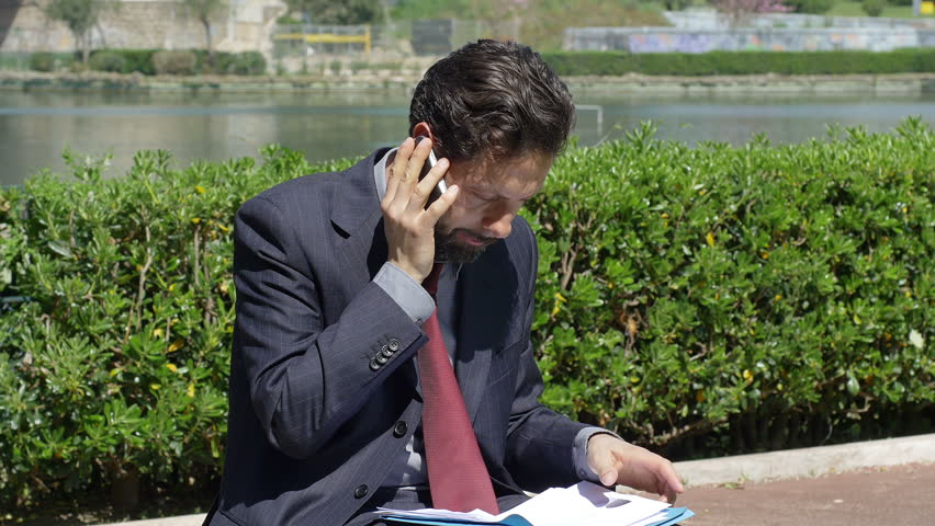young businessman working outdoor and having a phone call - 4K stock video clip