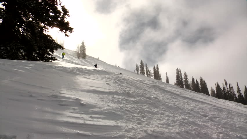 Two skiers on powder slope with Jupiter Peak in background, Park City, Utah. - HD stock footage clip