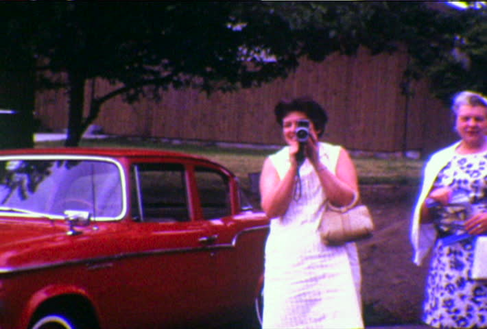 Seattle, Washington, Circa 1970s.  8mm home video of woman taking home movies with film camera, Seattle, Washington.