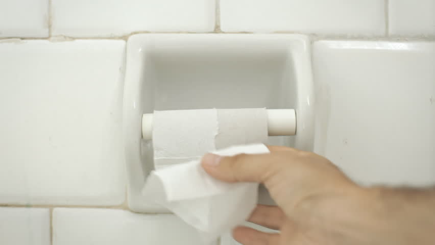 Someone grabs the last strip of paper from a toilet roll. It's useless as it's too short: what a bad surprise. Extreme close-up shot.