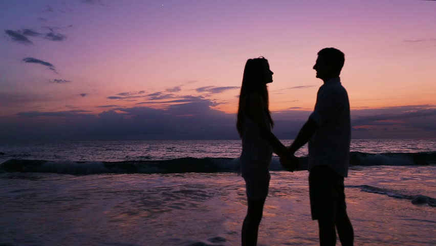 Romantic Couple Walks Towards Sunset Holding Hands Stock