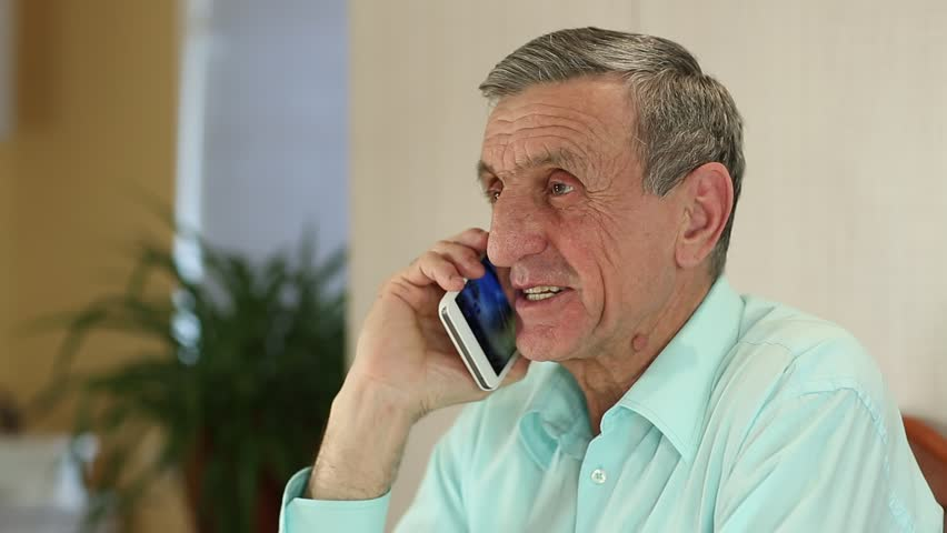 Senior man with white smartphone speaks and smiles. Man in blue shirt with mobile phone