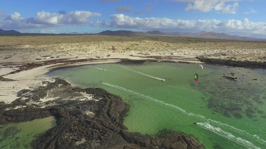 AERIAL: Flying above lots of kitesurfers kiteboarding in big flat lagoon on a beautiful summer day in sunny Fuerteventura