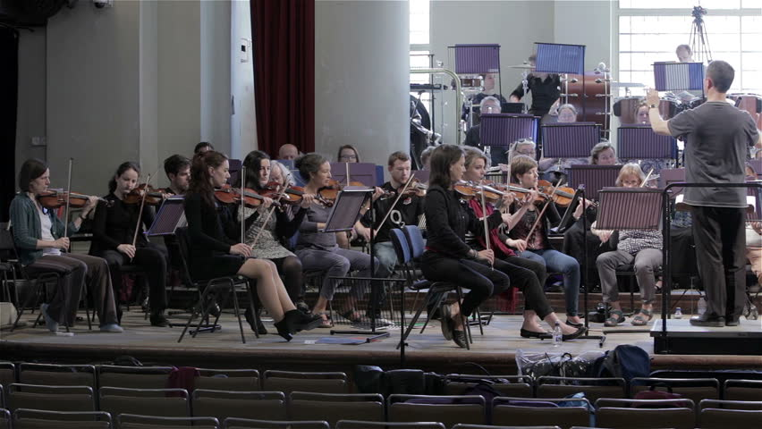 LONDON, UK - 8 JUNE 2013: Candid video footage and a slow pan across a full symphony orchestra during rehearsal.