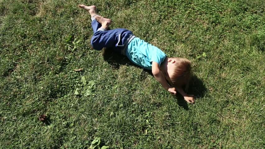 ANAPA, KRASNODAR REGION/RUSSIA - JULE 01: Girl and boy have fun somersault on grass lawn in the park on Jule 01, 2015 in Anapa  | Shutterstock HD Video #10939067