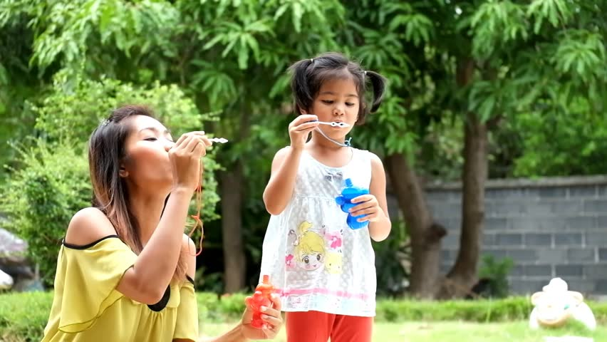 mother and daughter are blowing a soap bubbles, cute asian girl and mother playing soap bubbles - HD stock video clip