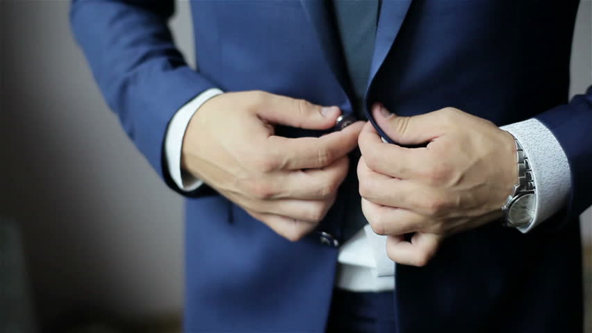 Buttoning a jacket. Stylish man in a suit fastening buttons on his jacket preparing to go out. Close up | Shutterstock HD Video #10977902
