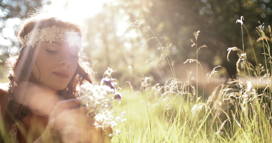 Beautiful hippie girl lying in green grass in a summer park holding some fresh wild flowers and wearing a vintage white lace headband with gentle sun flare