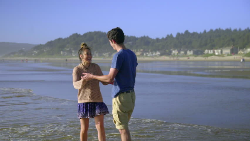 Attractive teenage boy and girl dance together in the ocean surf  - HD stock footage clip
