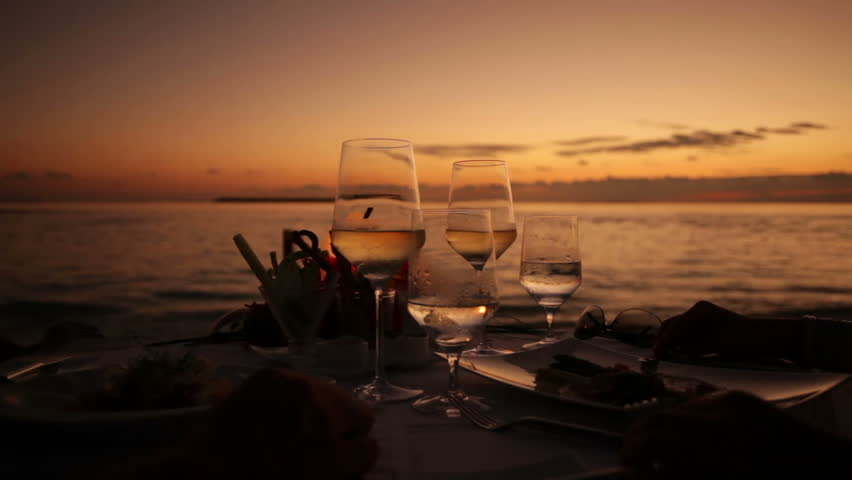 cheering with wine glasses at table on the beach during sunset with audio, close