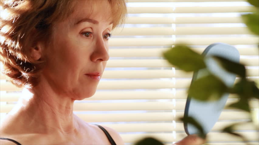 A mature woman looking in a mirror becomes dissatisfied and begins to examine her aging skin. - HD stock footage clip