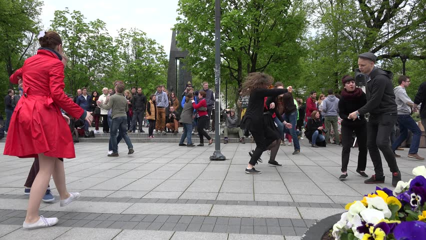 VILNIUS, LITHUANIA - MAY 16: Young dancers enjoy active lindy hop dance in pairs with strangers in street on May 16, 2015 in Vilnius, Lithuania. Street music day. Panorama shot. 4K - 4K stock video clip