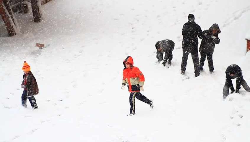 ISTANBUL - JAN 8, 2013: A giant snowstorm froze daily life as well as the streets all around the city. Children playing and gentle snow falling. Snowball fight while its snowing