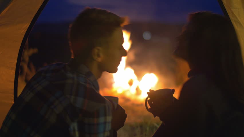 The pair sit and drink tea (coffee), talk, kiss and laughter in the camping tent by sky and bonfire background. Real time capture. Shot with crane and Red Cinema camera | Shutterstock HD Video #11059163