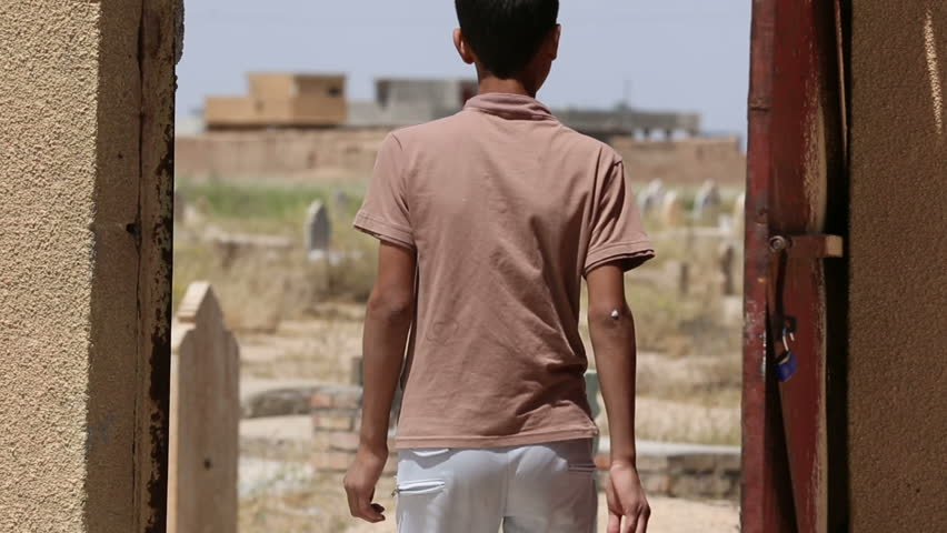AMERLI, IRAQ - MAY 2015: A boy enters cemetery's door. Amerli steadfastness to ISIS was a turning point in the war between Iraqi government and ISIS