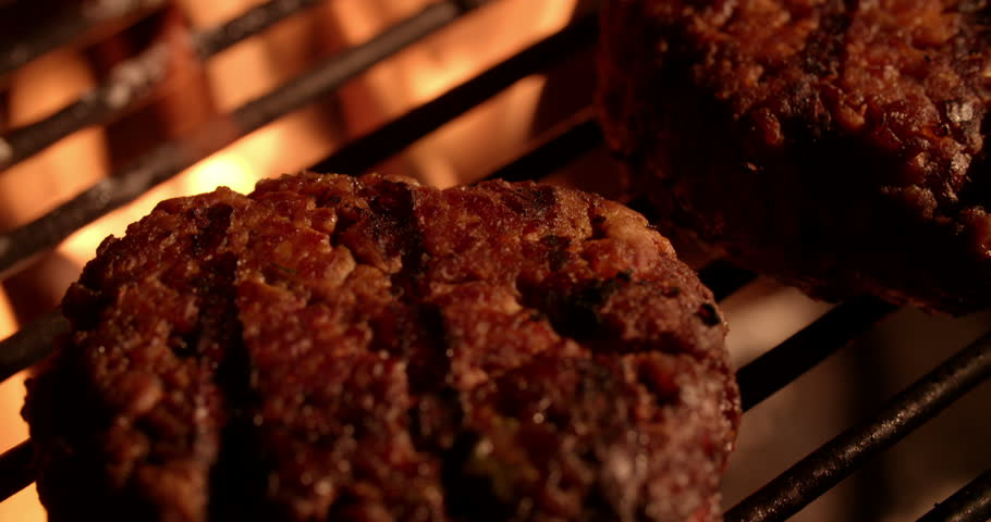 Two thick beef burger patties flame-grilling over glowing coals and flames of a night time outdoor barbecue in Slow Motion