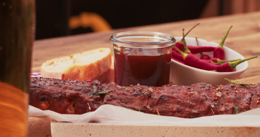 Person's hand painting a basting onto a tasty looking rack of ribs sprinkled with fresh rosemary on a wooden table with a jar of barbecue sauce and fresh red chillies, Panning in Slow Motion - 4K stock footage clip