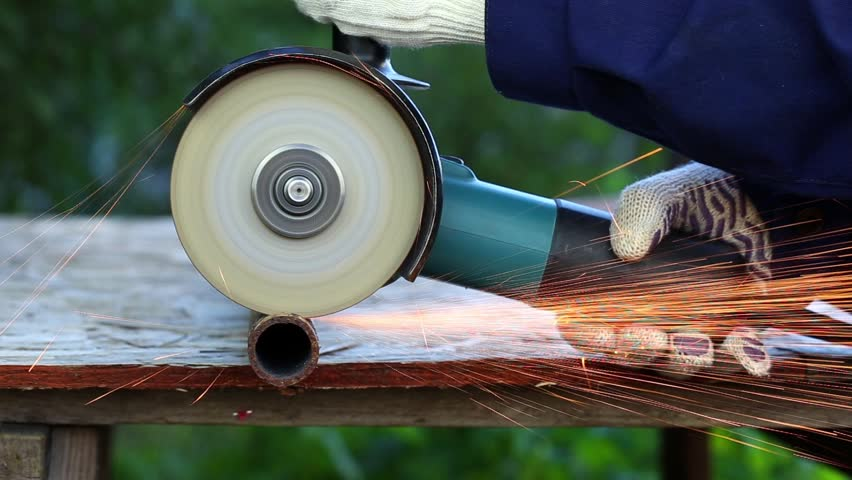 Worker in gloves cutting a metal pipe in two pieces with angle grinder