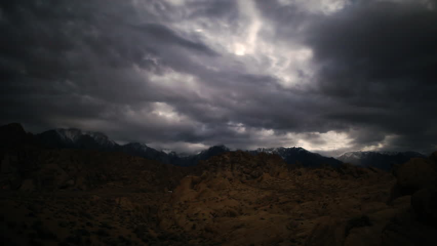 Astrophotography time lapse footage of overcast cloudscape giving way to starry sky over Sierra Nevada Mountains in California