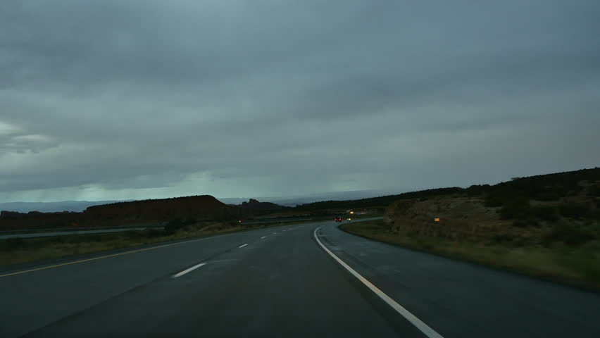 SAN RAFAEL DESERT, UTAH - JULY 2015: Point of View looking forward while driving the San Rafael desert of Utah following a summer rain as night starts to fall. | Shutterstock HD Video #11102696