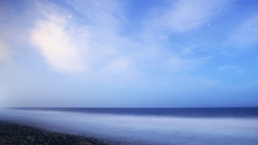 Astrophotography Time Lapse footage with pan right motion of Milky Way galaxy rising over Night Seascape with scattered clouds in Malibu Beach, California - 4K stock video clip
