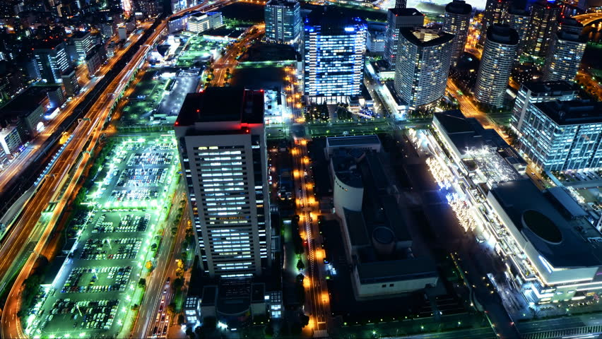 Time lapse footage with tilt up motion of metropolitan cityscape at night shot from Yokohama Landmark Tower in Japan