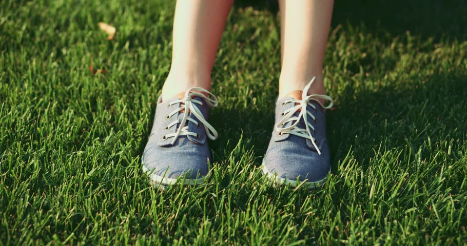 Female feet in sneakers gumshoes moving and posing on a sunlit green grass, close up. Woman's feet in blue jeans color sports shoes. Slow motion, 120fps. 4K, DCi. #11142575