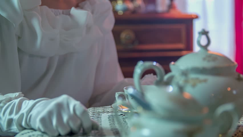Lady opens the lid of a sugar and picking up one cube and giving it to the man in to the tea, close up footage in slow motion.