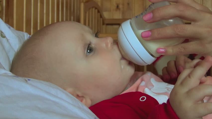 Seven month baby holds a bottle with milk and eats it - HD stock footage clip