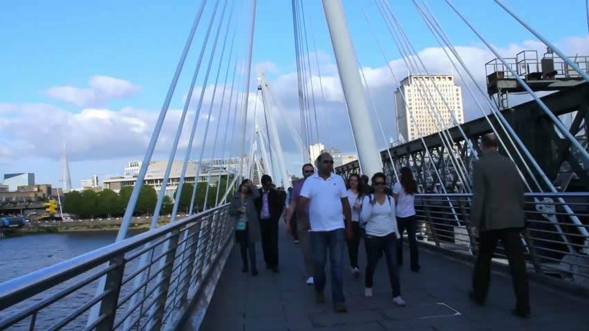 LONDON -JUNE 5: Unidentified tourists and locals on Haugerford Bridge over  the Thames in late afternoon light  on June 5, 2015 in London, UK. Time lapse - HD stock video clip