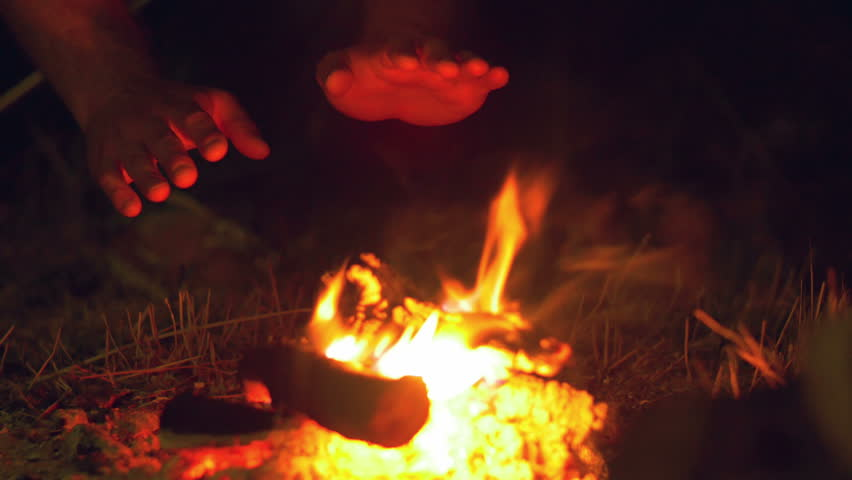 4 in 1 video! The man sit near bonfire and heat hands. Close up view. Shot with Red Cinema Camera - 4K stock footage clip