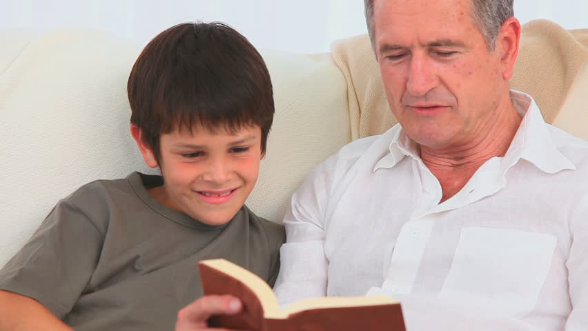 A lovely child listening to his grandfather reading a book - HD stock video clip